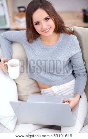 Woman sitting on the couch, she uses her laptop and hold a cup in  hand