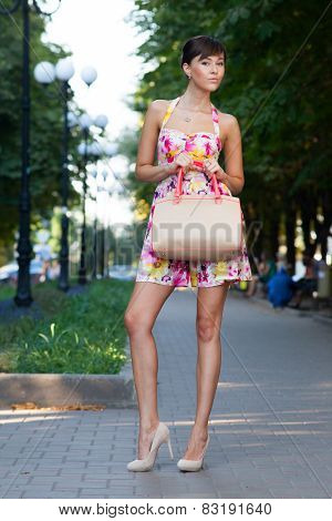 Happy Beautiful Model Standing On Street.flowered White Dress .beige Leather Handbag. High Heels