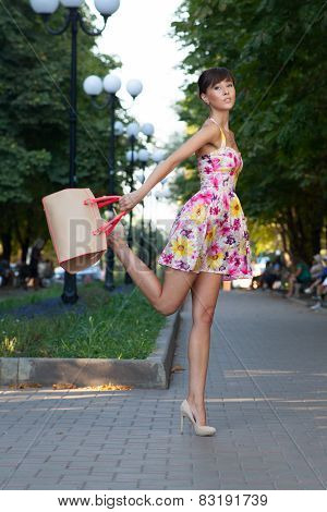 Happy Beautiful Model Jumping On Street.flowered White Dress .beige Leather Handbag. High Heels