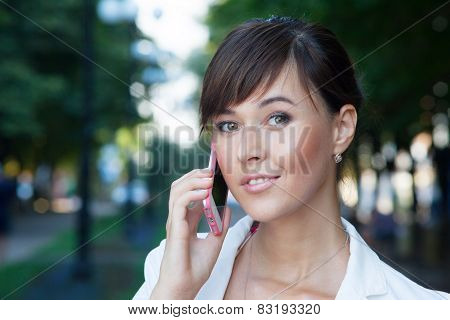 Closeup Portrait Of Beautiful Young Business Woman In White Jacket  Talking On Cellphone On The Stre