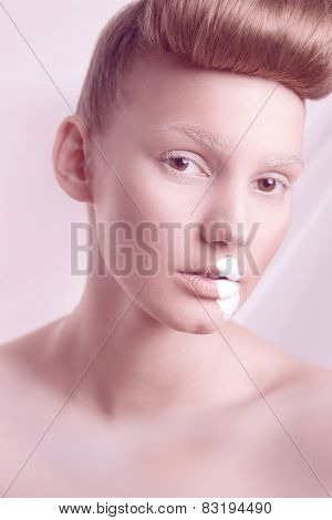 Closeup portrait of fashion model with hairstyle and pink ribbon of lipstick. Studio