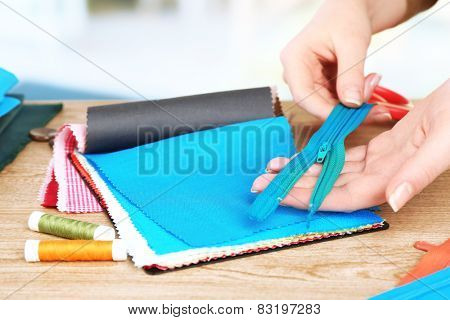 Colorful fabric samples and zipper in female hands on light blurred background