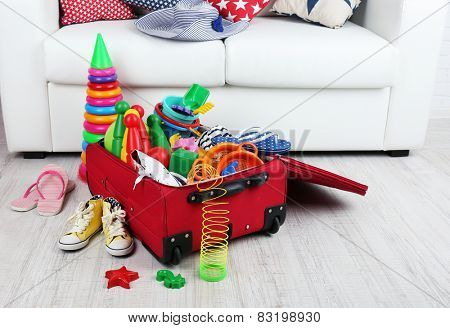 Suitcase packed with clothes and child toys on wooden floor and white sofa background