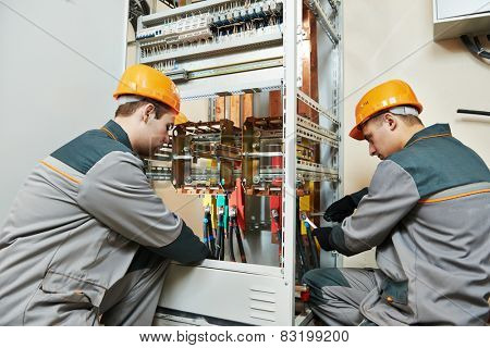 two electrician builder engineer works with electric cable wiring of fuse switch box