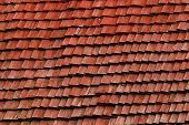 stock photo of shingles  - weather beaten red shingle roof made of wood - JPG
