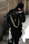 stock photo of extremist  - Armed criminal in black mask standing on the staircase - JPG