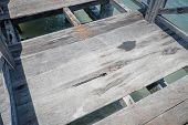 stock photo of unsafe  - Unsafe boardwalk over the sea with missing parts  - JPG