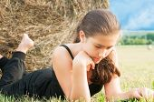 stock photo of haystack  - Girl with device laying on the field close to haystack - JPG