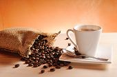 stock photo of hot coffee  - Cup of hot coffee on wood table and sack with coffee beans with orange background - JPG