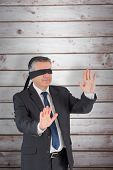 stock photo of blindfolded man  - Mature businessman in a blindfold against wooden planks - JPG