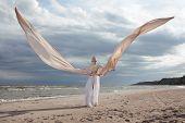 stock photo of long beach  - female model in extreme long beige dress posing dynamic in the beach - JPG