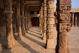 image of qutub minar  - Columns with stone carving in courtyard of Quwwat - JPG