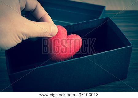 Human Hand Holding Or Putting A Red Heart-shaped In A Black Gift Box