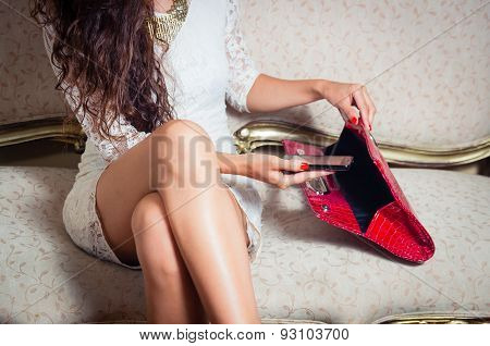 Pretty model girl sitting on victorian sofa posing for camera