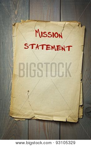 Mission statement. Old paper on a wooden background