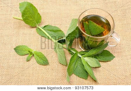 Fresh Green Mint And Cup Of Beverage On Burlap Texture
