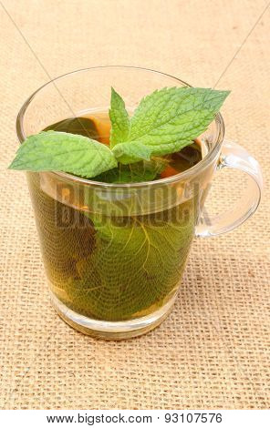 Fresh Green Mint In Cup Of Beverage On Burlap Texture