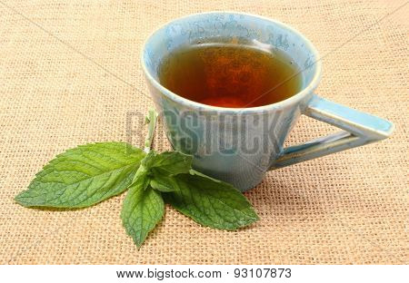 Fresh Green Mint And Cup Of Beverage On Jute Canvas