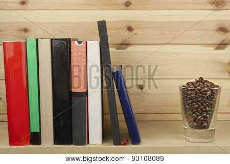 Shelf with different colored book on a wooden background