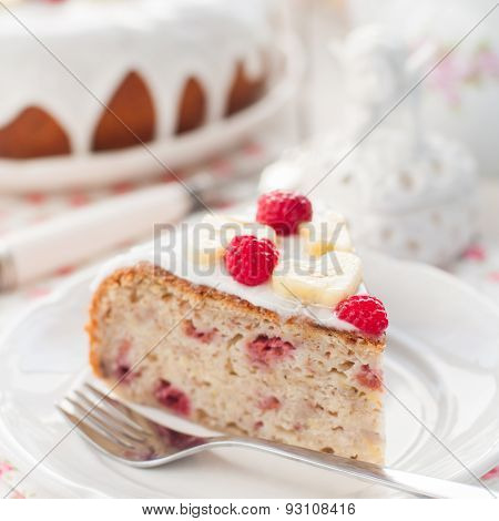 Banana Cake With Sugar Glaze Topped With Raspberries And Banana Slices