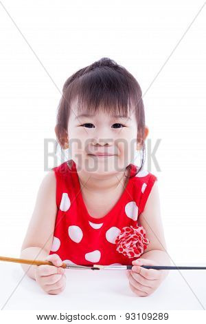 Child Looking At The Camera And Smiling, Holding A Paintbrushs. Isolated On White