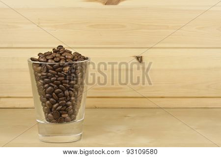 glass with coffee beans standing on a wooden shelf.
