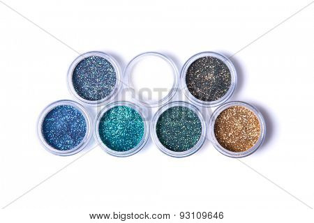Two rows of metallic glitters in jars, top view isolated on white background