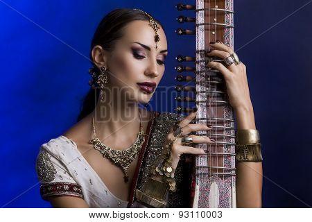 Beautiful Indian Woman In Sari With Oriental Jewelry Playing The Sitar