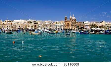 Maltese Fishing Village With Boats And Church