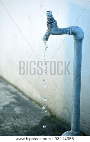 Tap of running water isolated on grey background