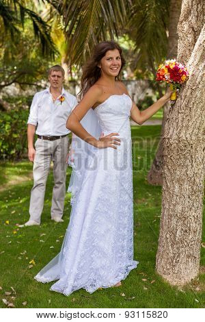 Bride And Groom On The Background Of Palm Trees