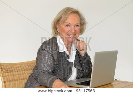 Senior Woman In Business Look In Front Of A Silver Laptop