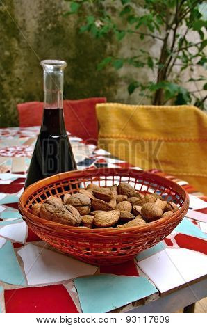 Almonds and walnuts in basket on mosaic table
