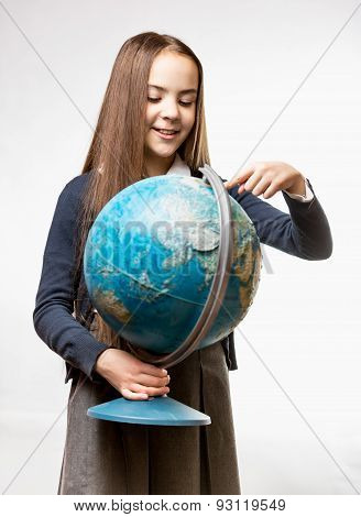 Smiling Girl In School Uniform Pointing At Earth Globe