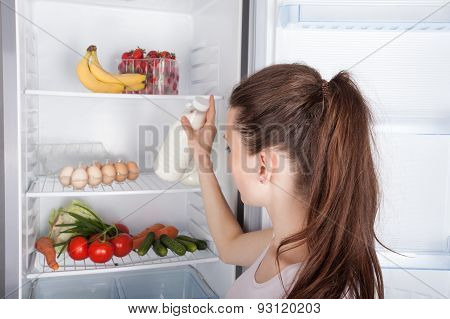 Woman Chosen Milk In Opened Refrigerator