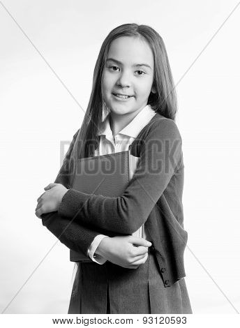 Black And White Portrait Of Smiling Schoolgirl Posing With Book