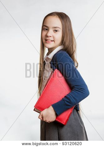 Portrait Of Smiling Brunette Schoolgirl Holding Big Book