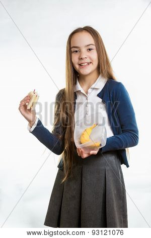 Girl Taking Sandwich Out Of Lunchbox Against White Background
