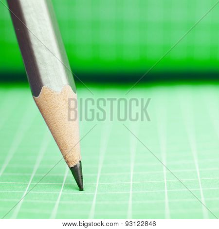 Sharp wooden pencil on green checkered paper