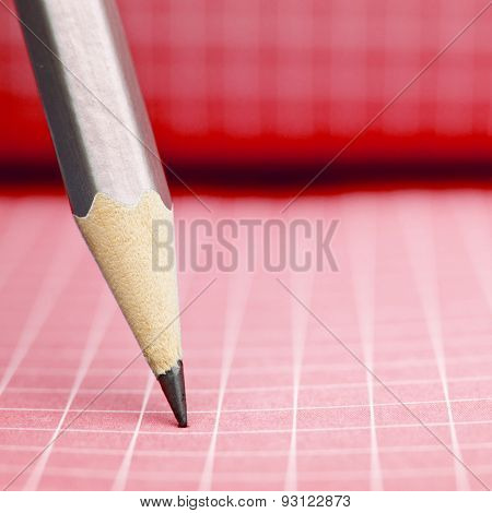 Sharp wooden pencil on red checkered paper