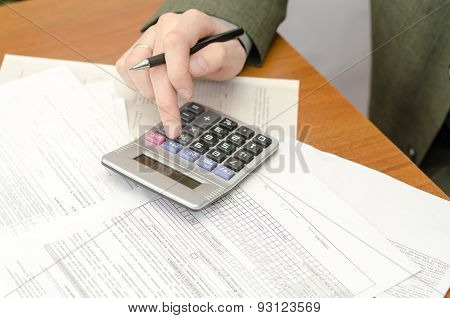 The Businessman During Office Work With Documents And The Calculator