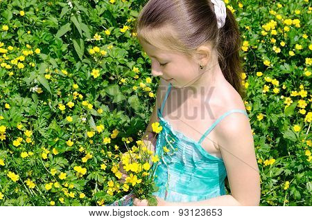 The Child Sits On A Glade And Holds Flowers