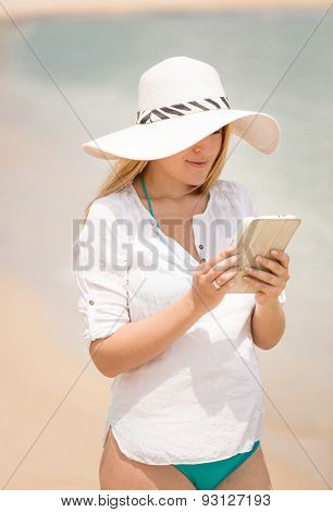Young Woman Working On Digital Tablet At Beach At Windy Day