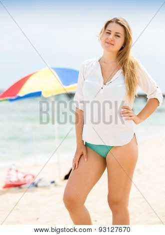 Beautiful Woman In White Shirt Posing On Beach Against Parasols