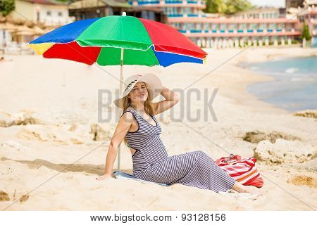 Woman Awaiting For Baby Relaxing On The Beach At Hot Sunny Day