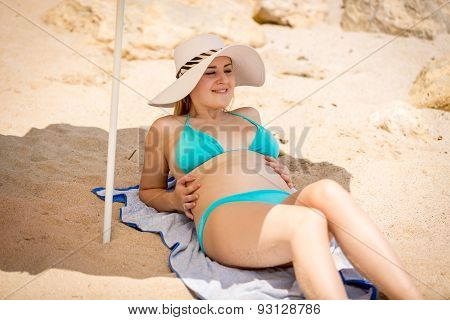 Young Woman In Hat And Blue Bikini Relaxing On Beach Under Parasol