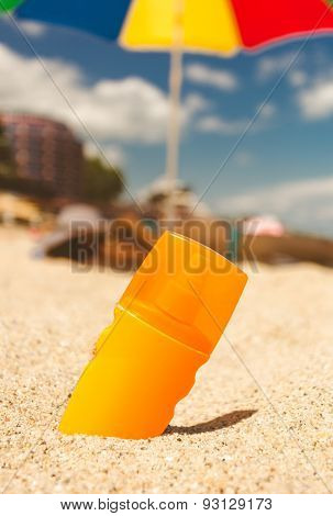 Toned Photo Of Suntan Lotion On Sandy Beach At Sunny Day