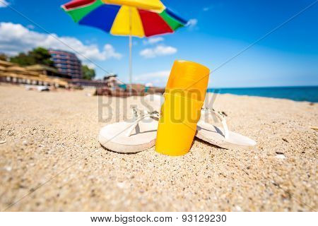 Closeup Of Yellow Suntan Lotion And Flip Flops Lying On Sandy Beach