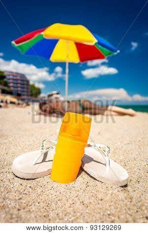Closeup Shot Of Flip-flops And Sunblock Lotion Lying On Beach