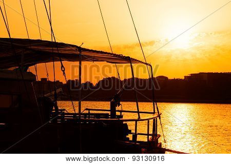 Silhouette Of A Fishing Boat In A Harbor At Sunset